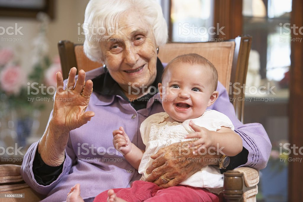 Grandmother holding her granddaughter on lap stock photo