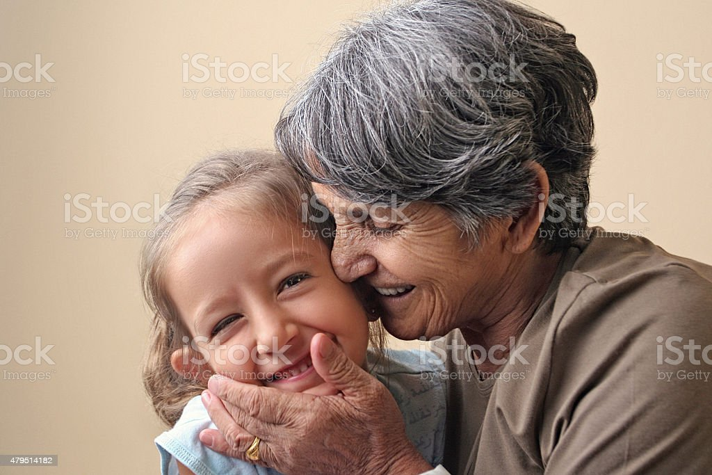 Grandmother hugging and kissing granddaughter stock photo