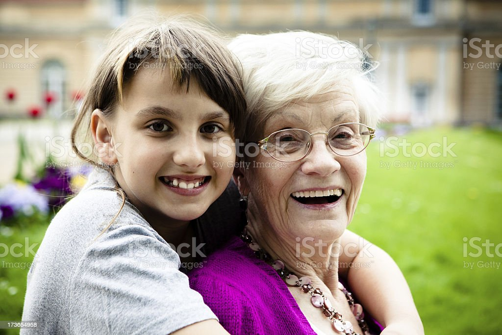 grandmother hugging granddaughter, arms around royalty-free stock photo