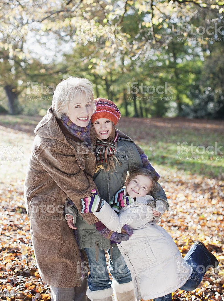 Grandmother hugging granddaughters outdoors in autumn royalty-free stock photo