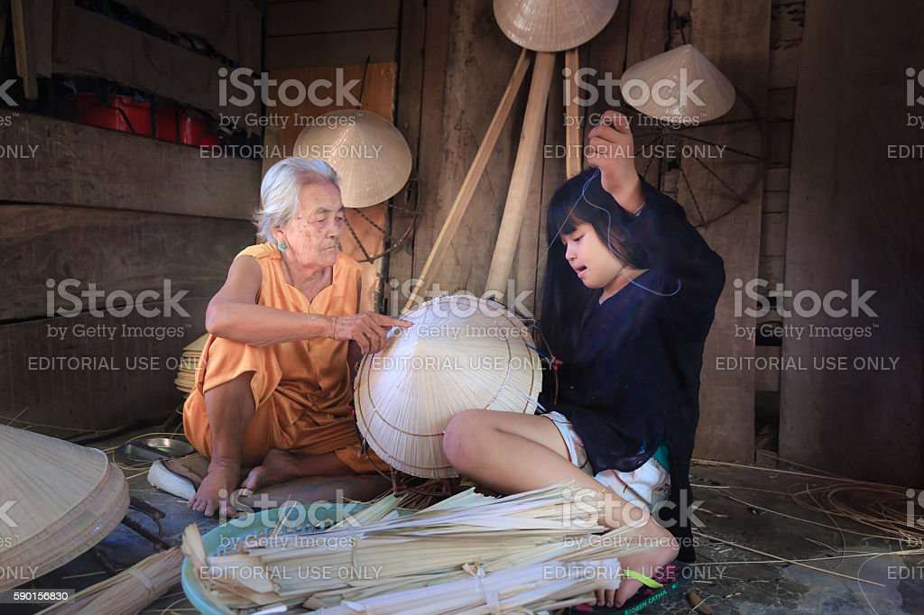 grandmother is teaching granddaughter how to sew traditional conical hat stock photo