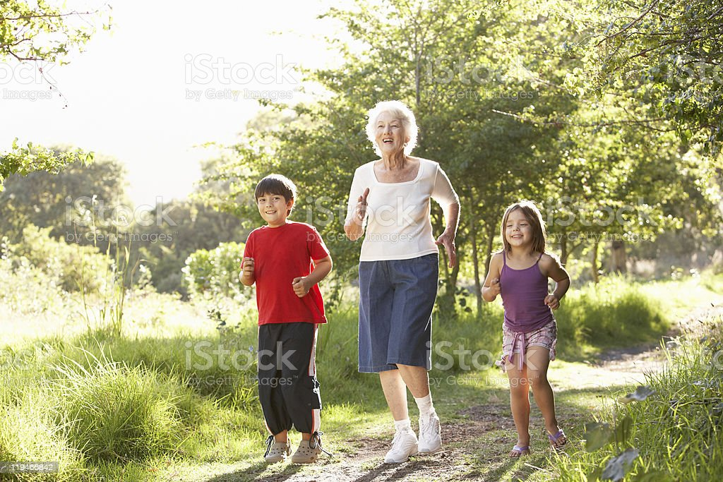 Grandmother Jogging In Park With Grandchildren royalty-free stock photo