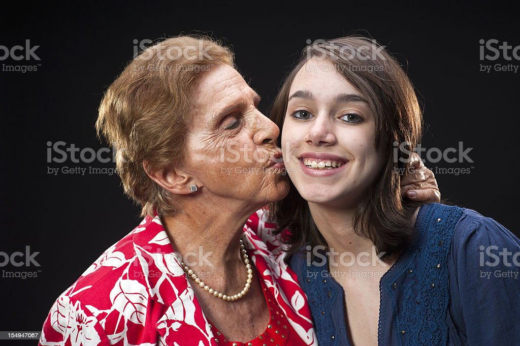 Grandmother kissing her granddaughter royalty-free stock photo