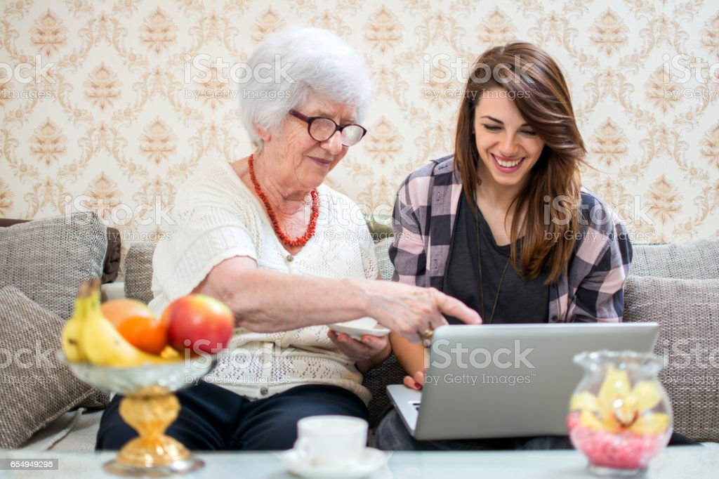 Grandmother looking at laptop with her granddaughter at home. stock photo