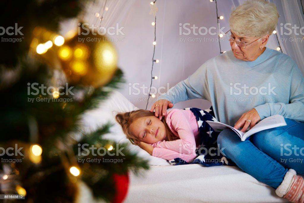 Grandmother lull granddaughter to sleep stock photo