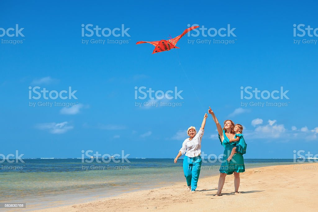 Grandmother, mother, and child launching kite on ocean beach stock photo