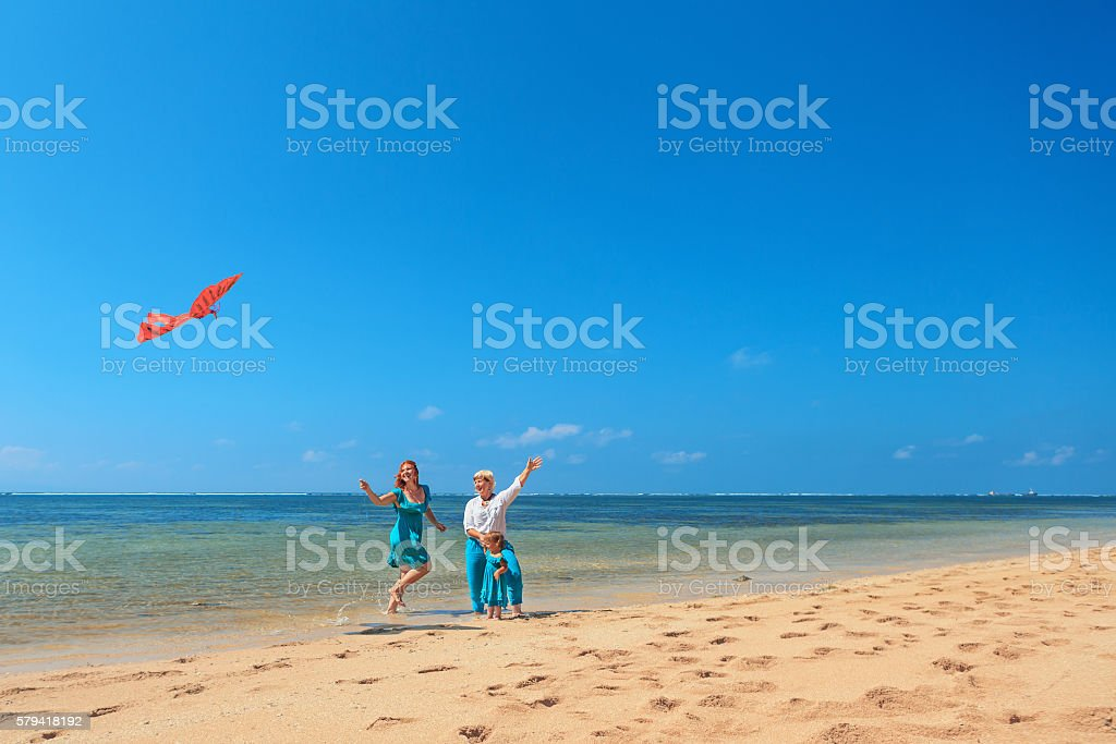 Grandmother, mother, and child launching kite on sea beach stock photo