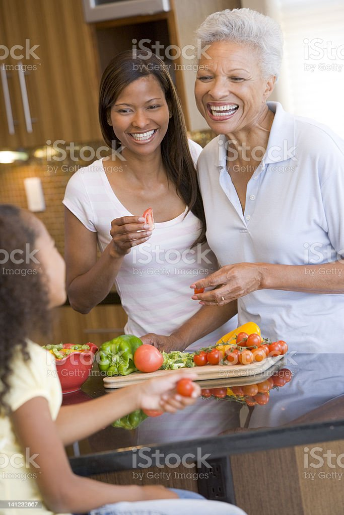 Grandmother, Mother And Daughter Preparing Meal Together royalty-free stock photo