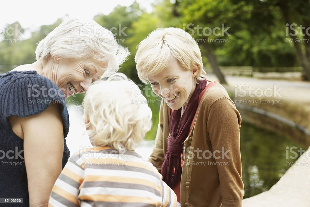Grandmother, mother and son sitting near pond royalty-free stock photo