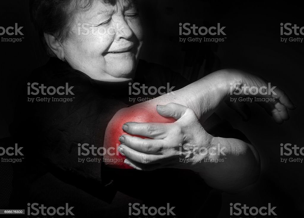 grandmother, old woman holding her arm, shoulder, elbow,  pain, stock photo