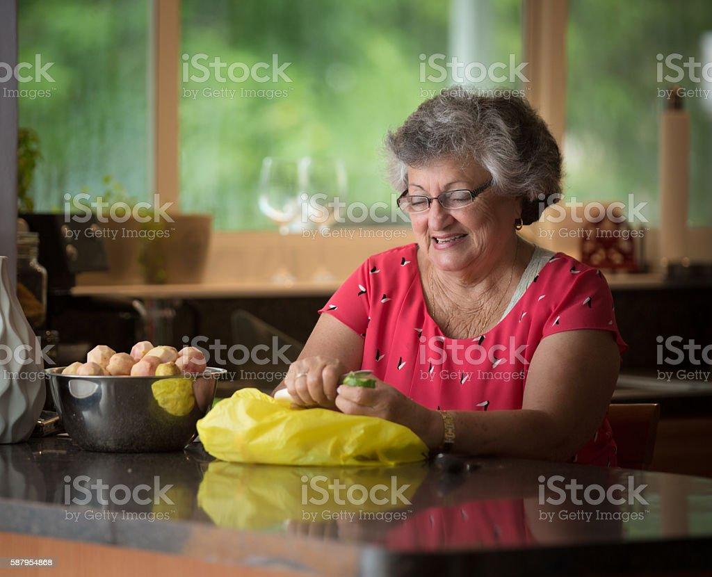 Grandmother peeling fruit for a dessert stock photo