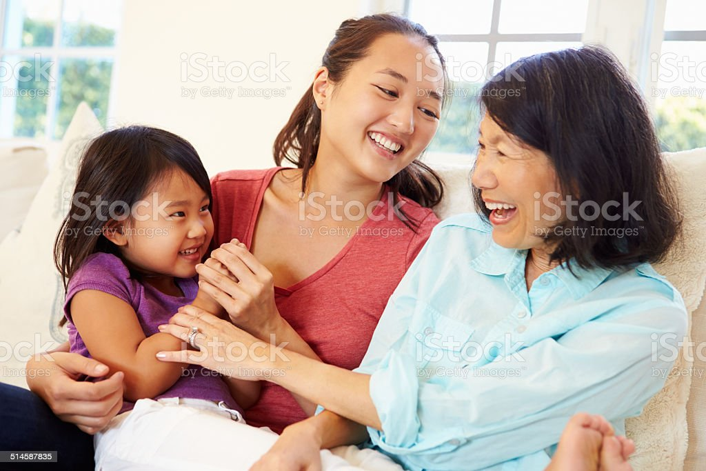 Grandmother Playing On Sofa With Granddaughter And Daughter stock photo