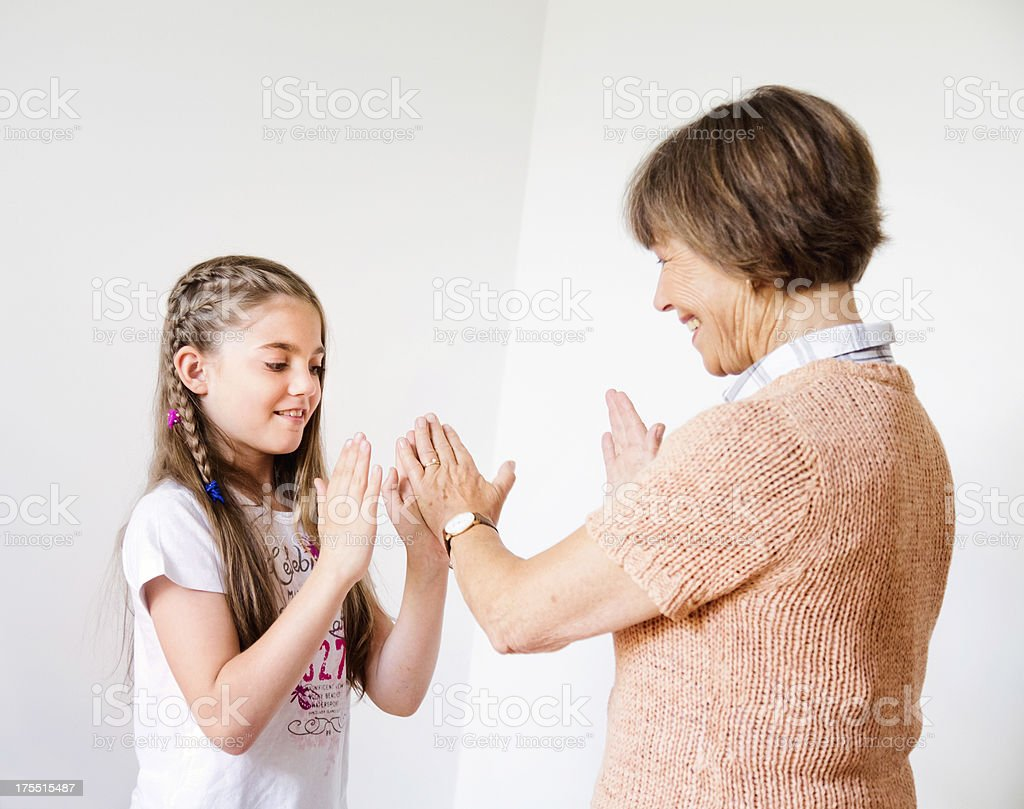 Grandmother playing patty cake with her granddaughter stock photo