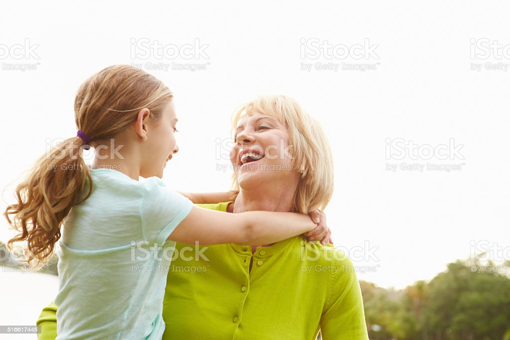 Grandmother Playing With Granddaughter Outdoors stock photo