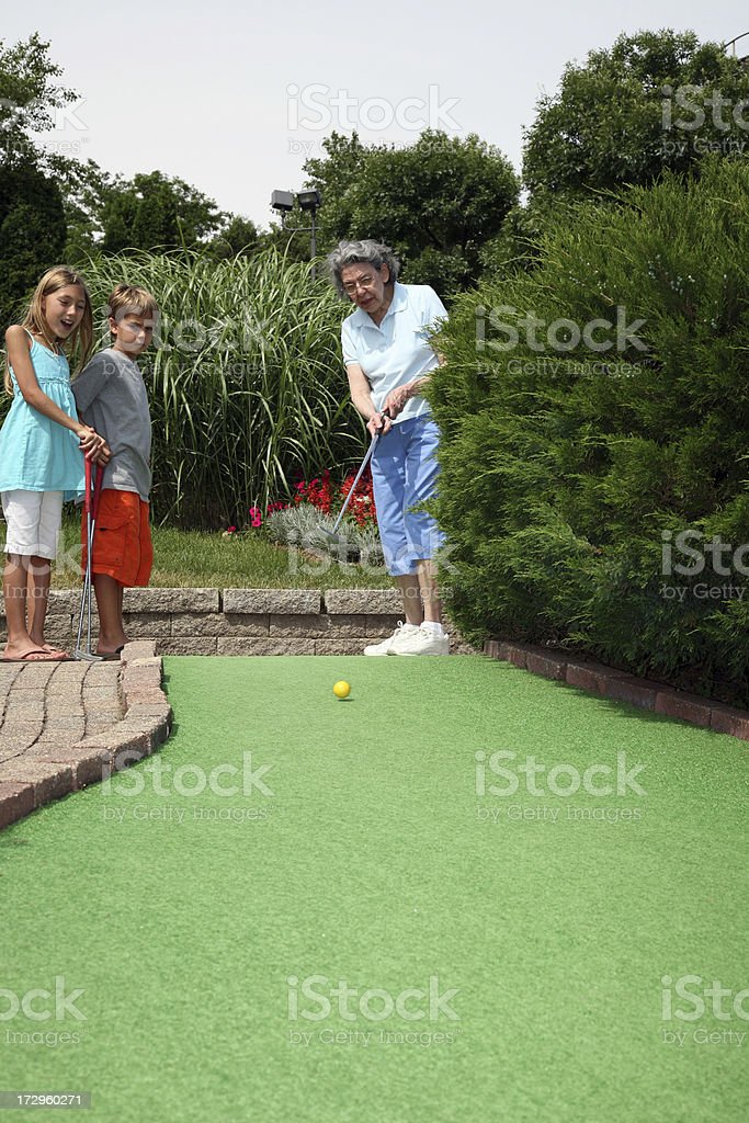 Grandmother plays miniature golf with grand kids royalty-free stock photo
