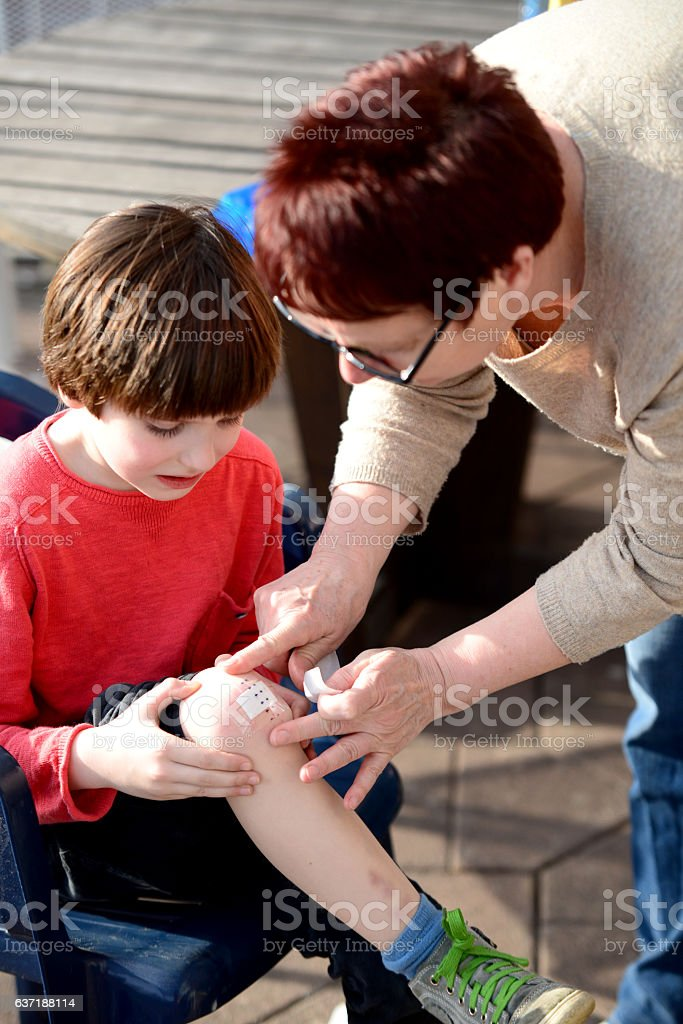 Grandmother puts plaster on grandsons elbow stock photo
