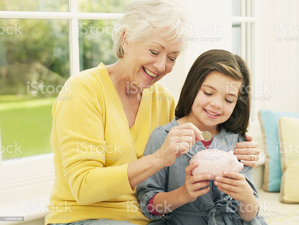 Grandmother putting coin into granddaughters piggy bank royalty-free stock photo