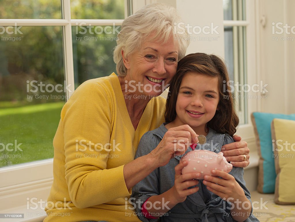 Grandmother putting coin into granddaughter's piggy bank royalty-free stock photo