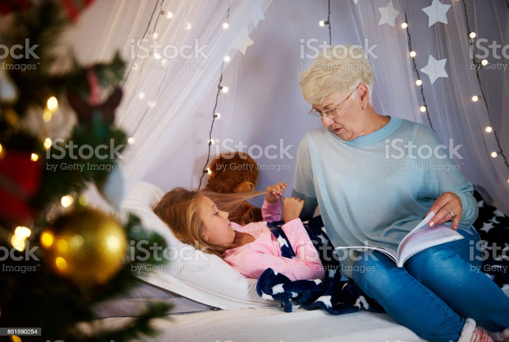 Grandmother reading a storybook to granddaughter stock photo