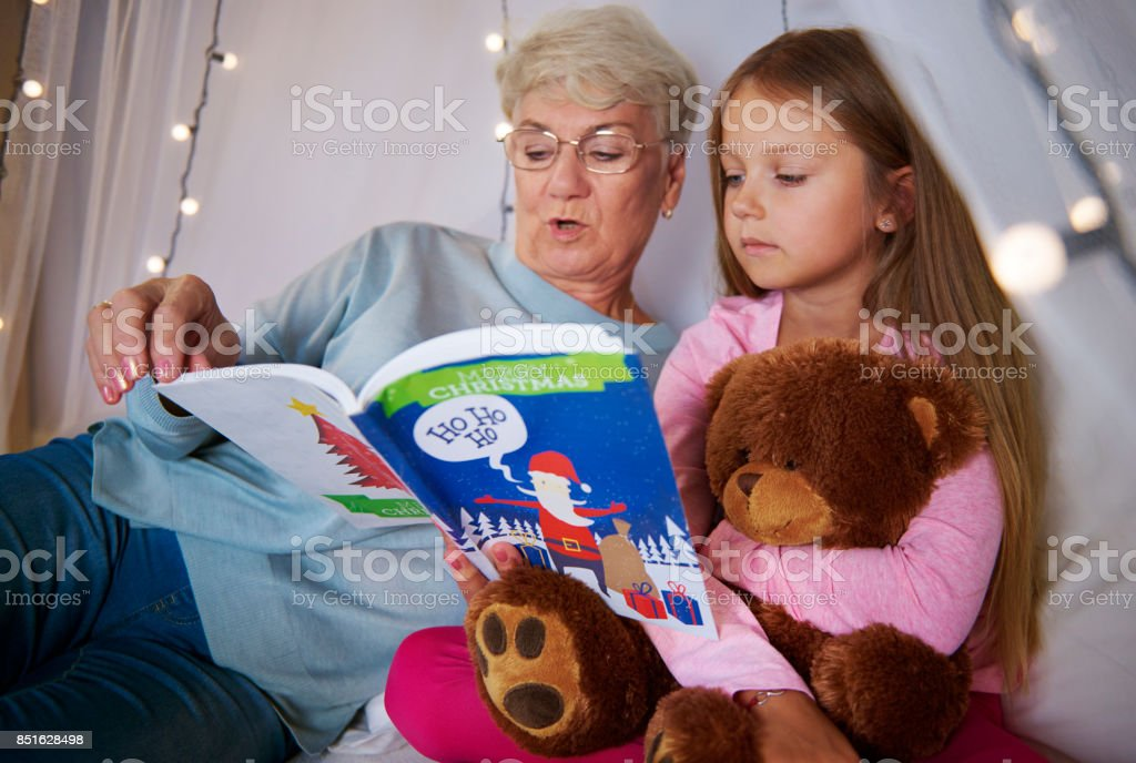 Grandmother reading book out to her granddaughter stock photo