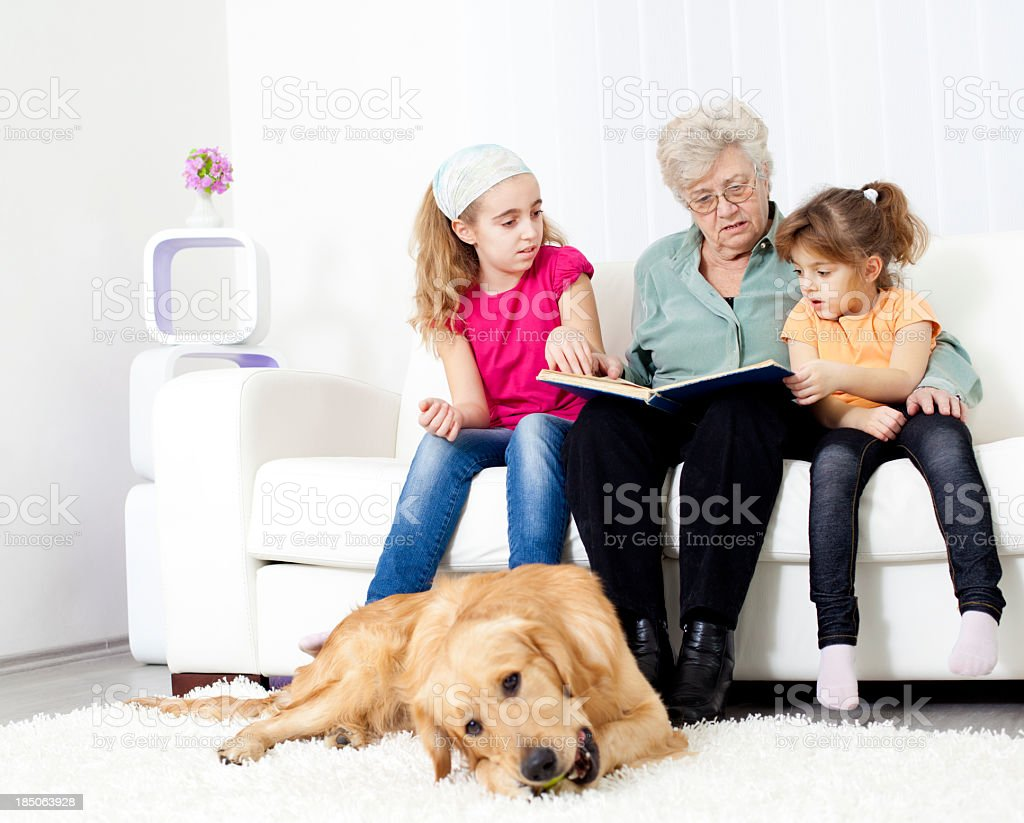 Grandmother Reading Book To Her Granddaughters royalty-free stock photo
