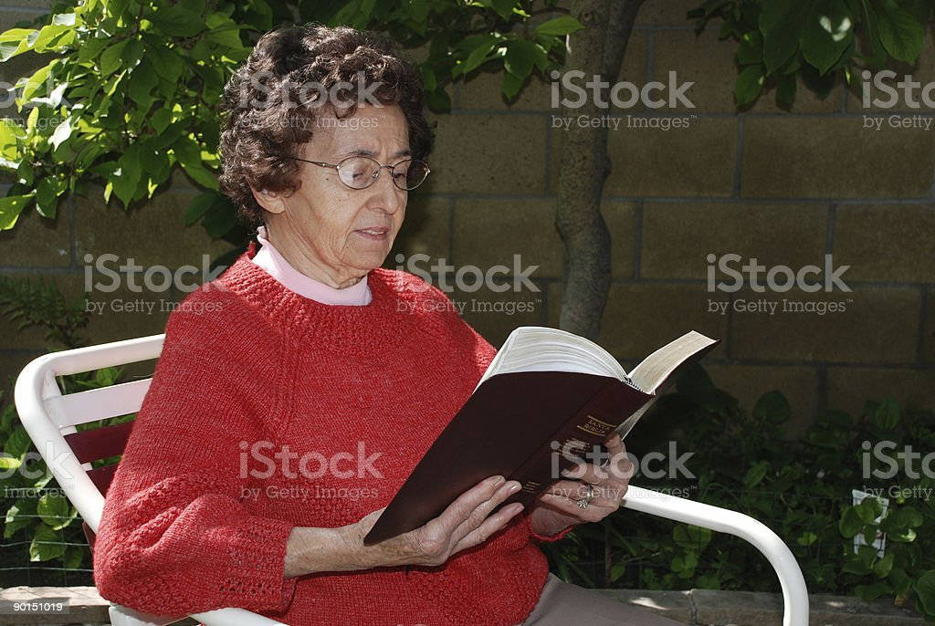 Grandmother Reads Words of Comfort from the Bible royalty-free stock photo