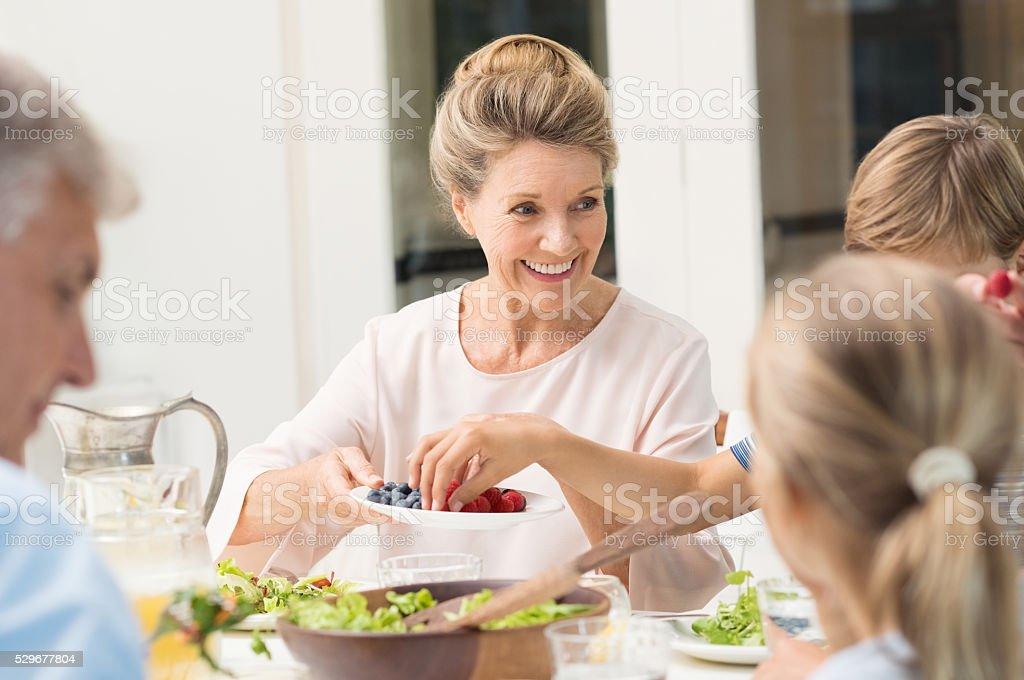 Grandmother serving food stock photo