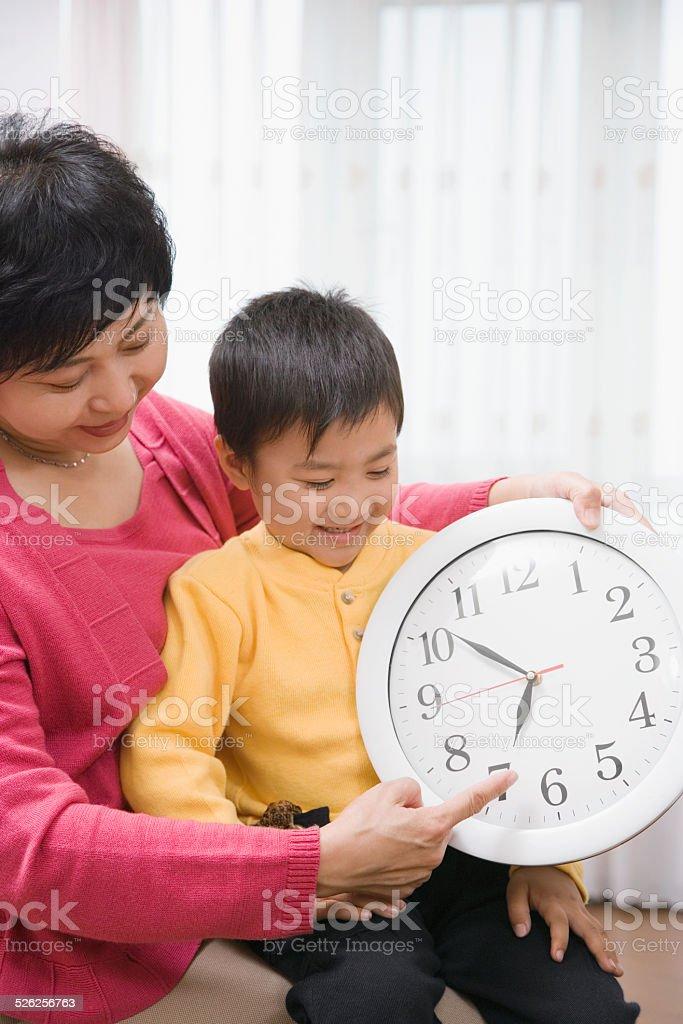 Grandmother showing grandson (4-5) clock stock photo