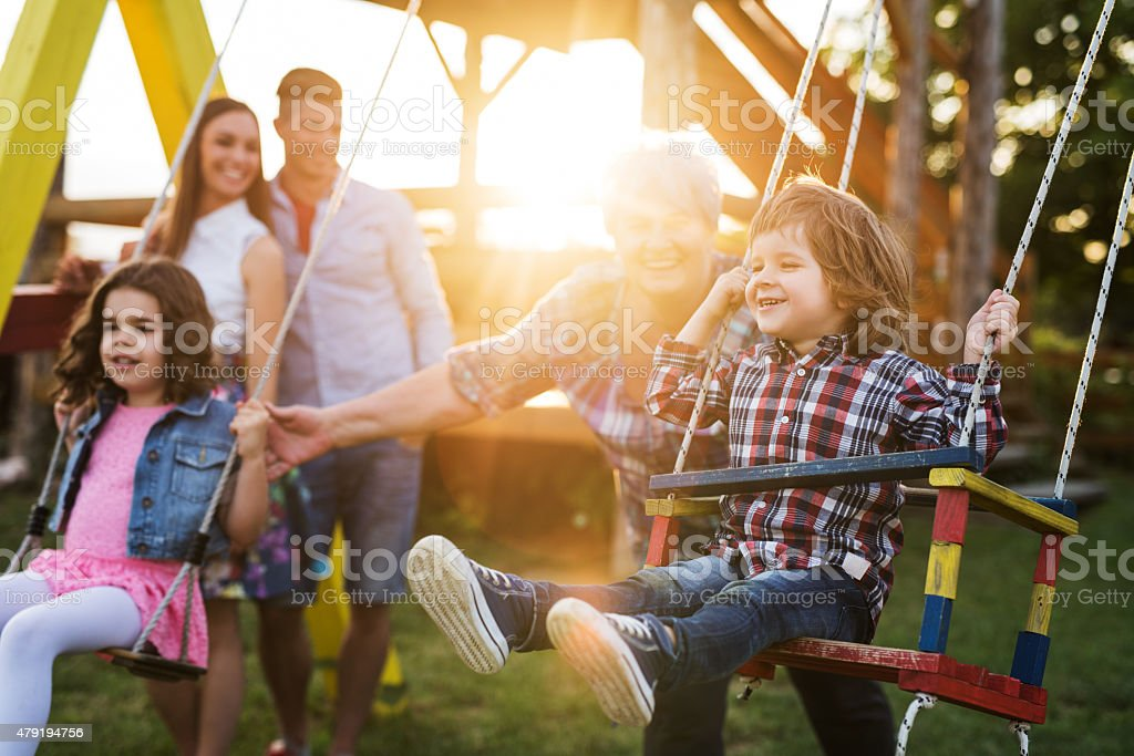 Grandmother swinging her grandchildren at sunset. stock photo
