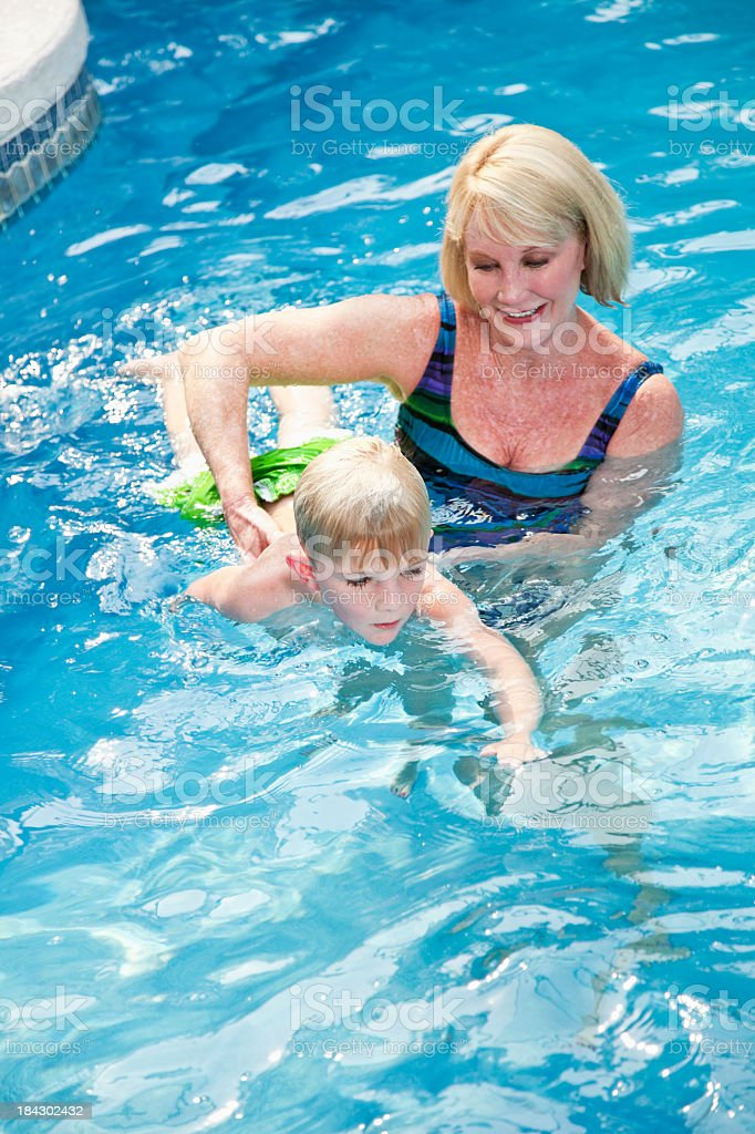 Grandmother teaching little boy to swim stock photo
