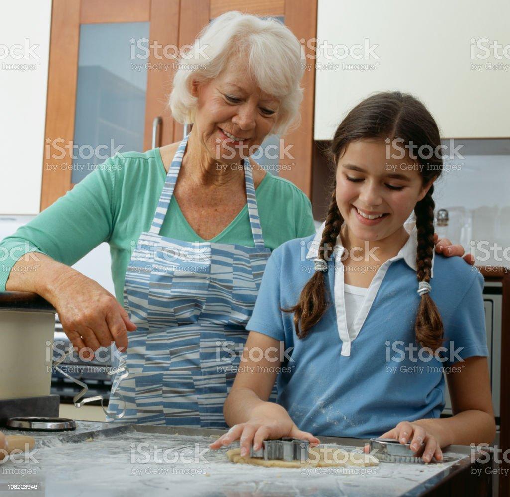 Grandmother Teaching Young Girl to Bake stock photo