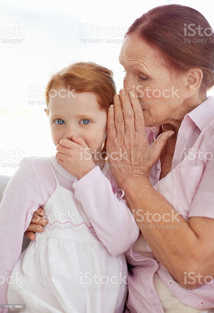 Grandmother telling a secret to her granddaughter stock photo