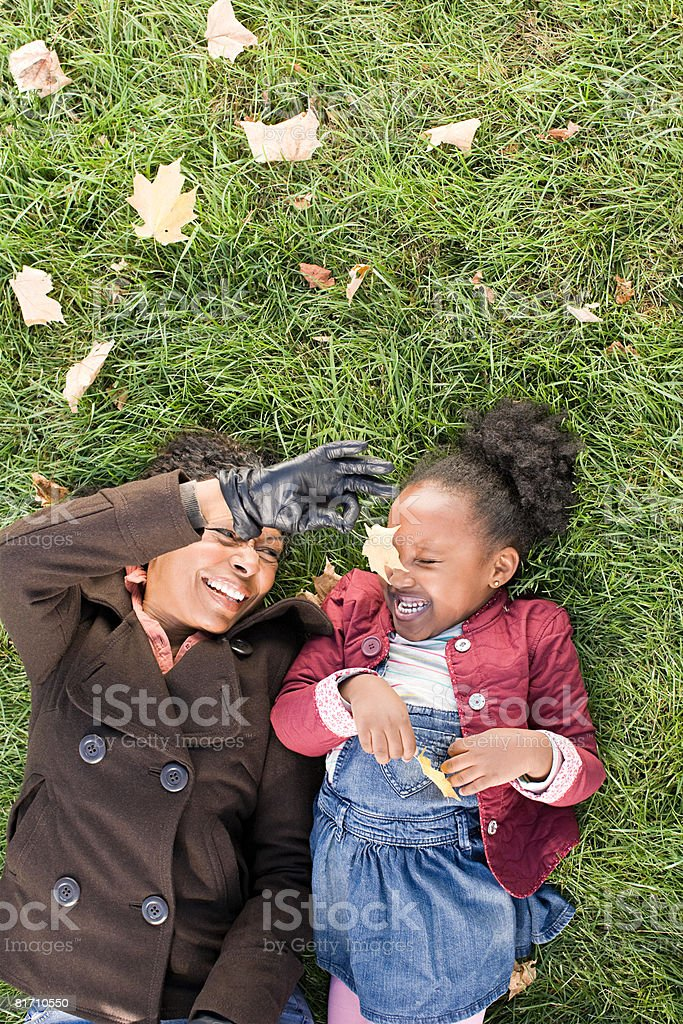 A grandmother tickling her granddaughters nose with a leaf royalty-free stock photo