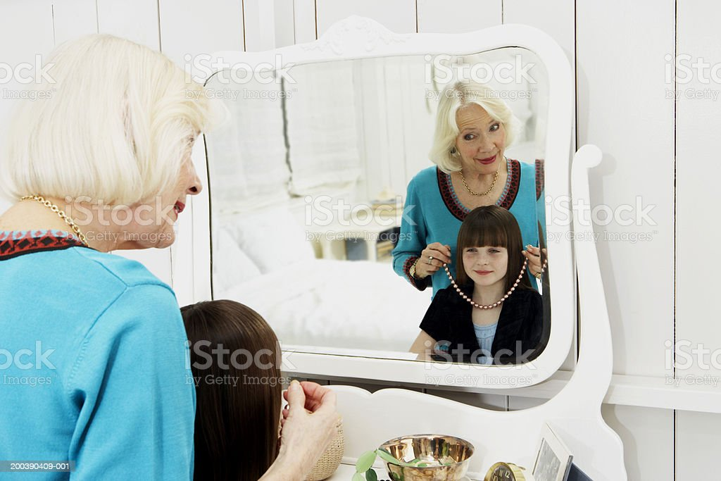 Grandmother (2-4) trying necklace on granddaughter (8-10) in mirror royalty-free stock photo