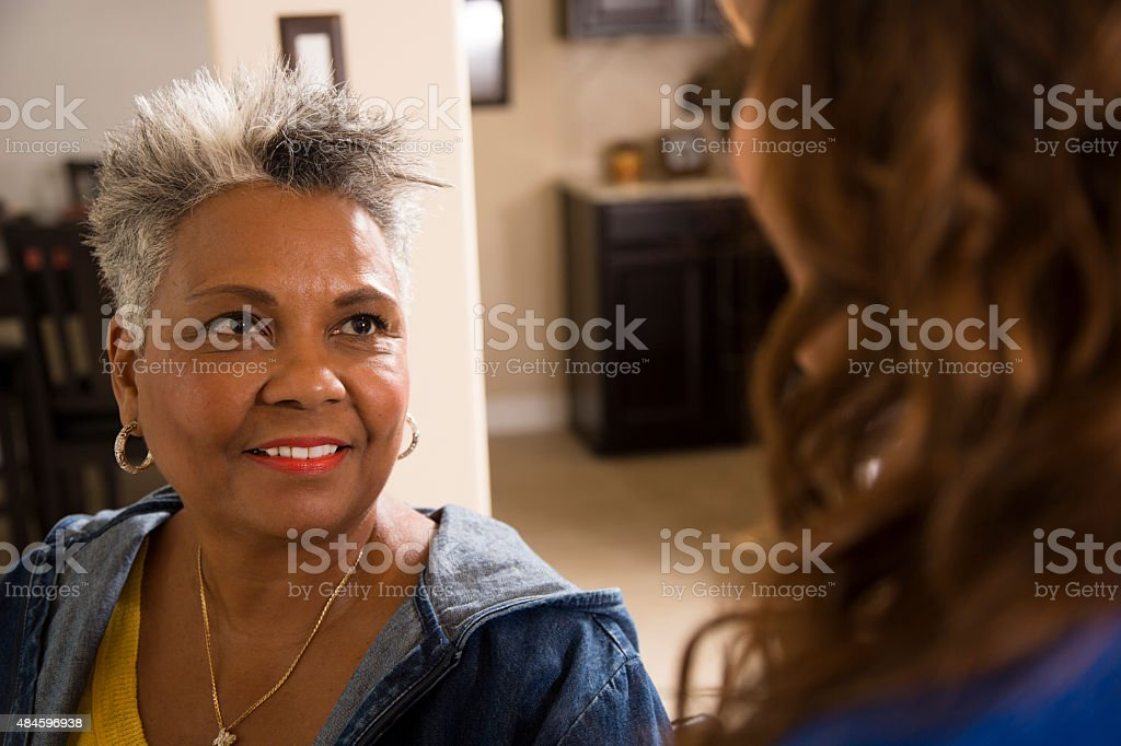 Grandmother visits with granddaughter in a nursing home. stock photo