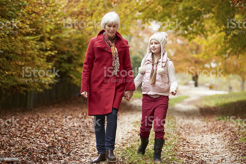 Grandmother Walking Along Autumn Path With Granddaughter royalty-free stock photo