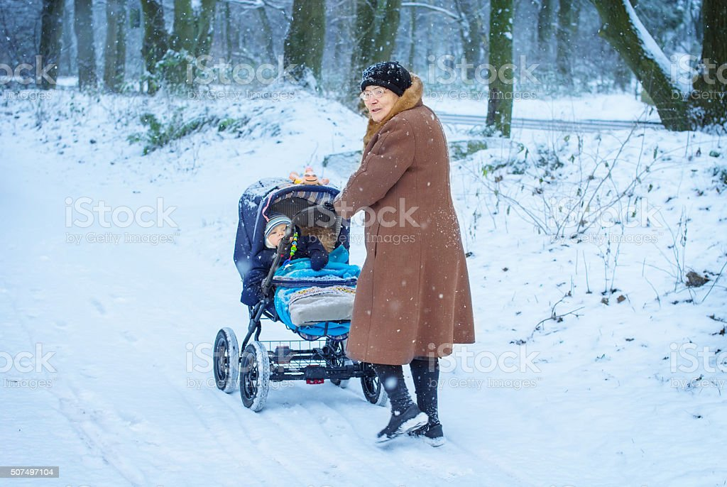 Grandmother walking with baby boy  in winter stock photo