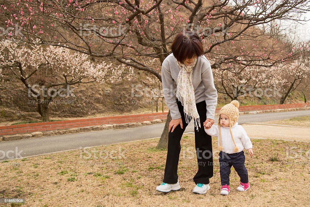 Grandmother walking with granddaughter stock photo