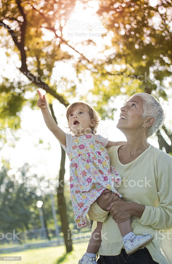 Grandmother with grand daughter in park stock photo