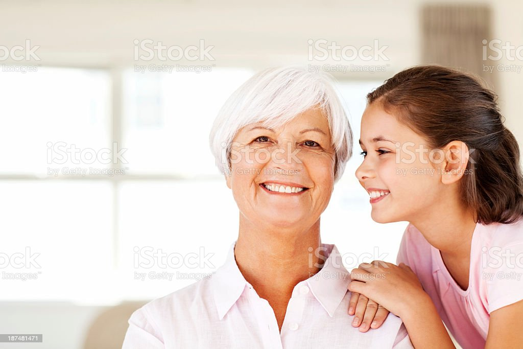 Grandmother With Granddaughter About To Kiss Her On Cheek royalty-free stock photo