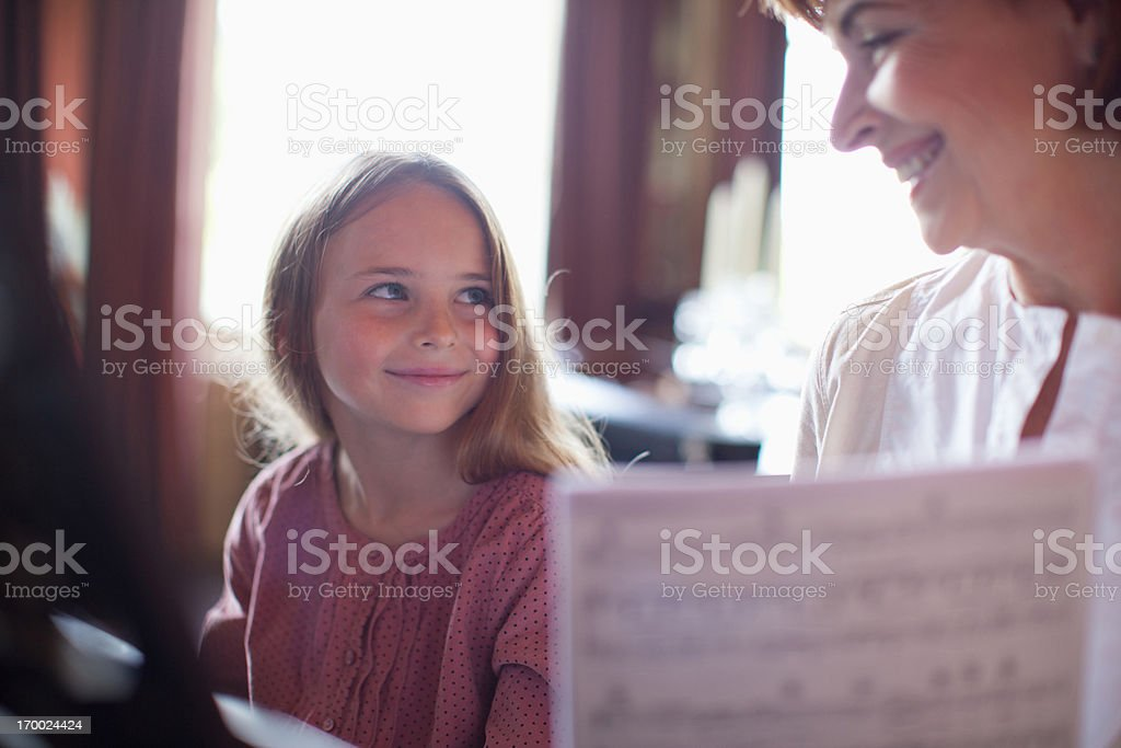 Grandmother with granddaughter practice on recorder royalty-free stock photo