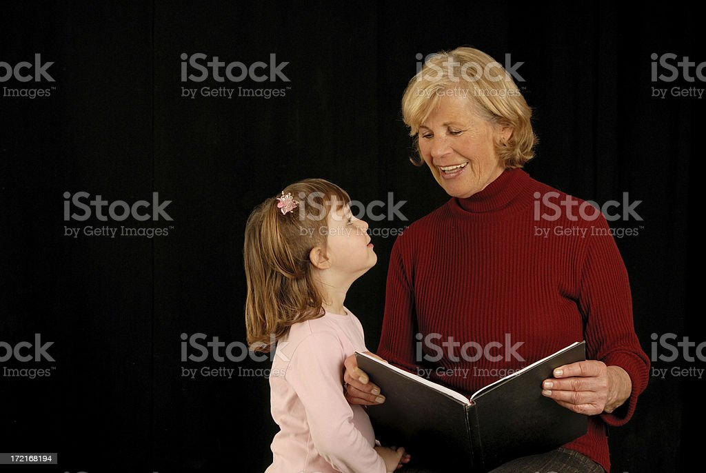 grandmother with granddaughter reading royalty-free stock photo