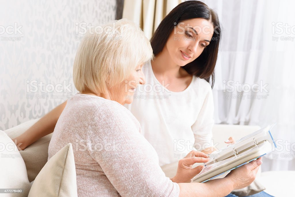 Grandmother with her daughter holding book stock photo