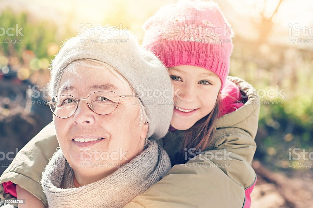 Grandmother with her grandaughter smiling. stock photo