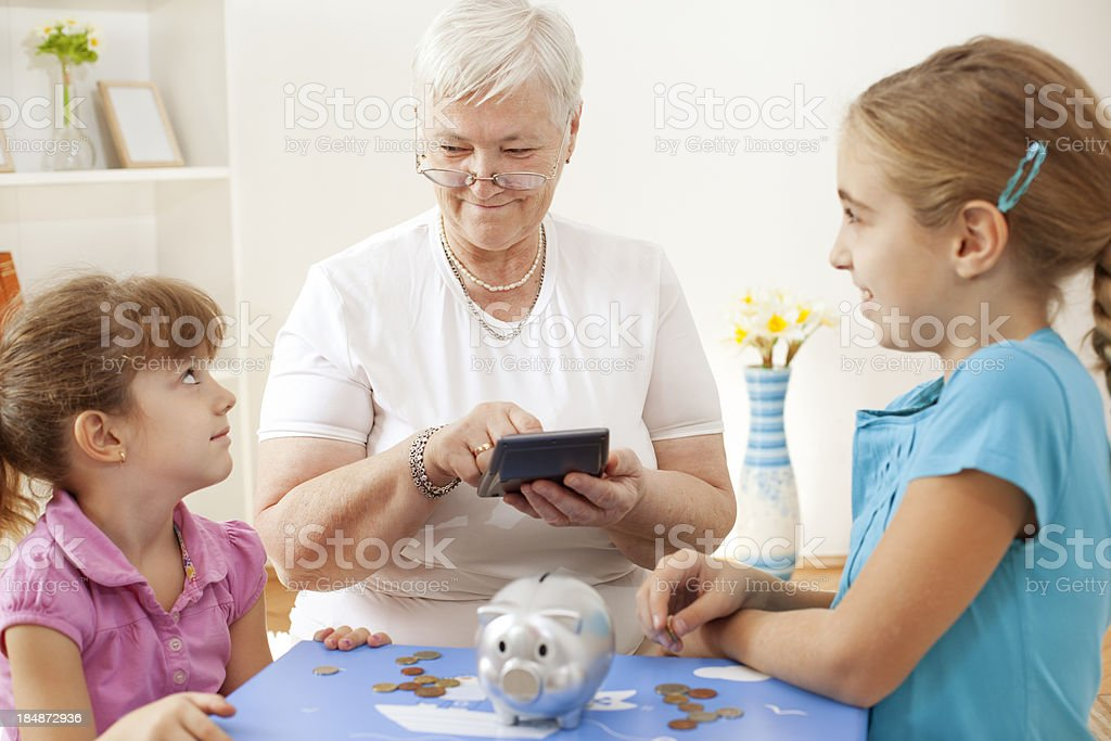 Grandmother with her grandchildren counting money in piggy bank royalty-free stock photo