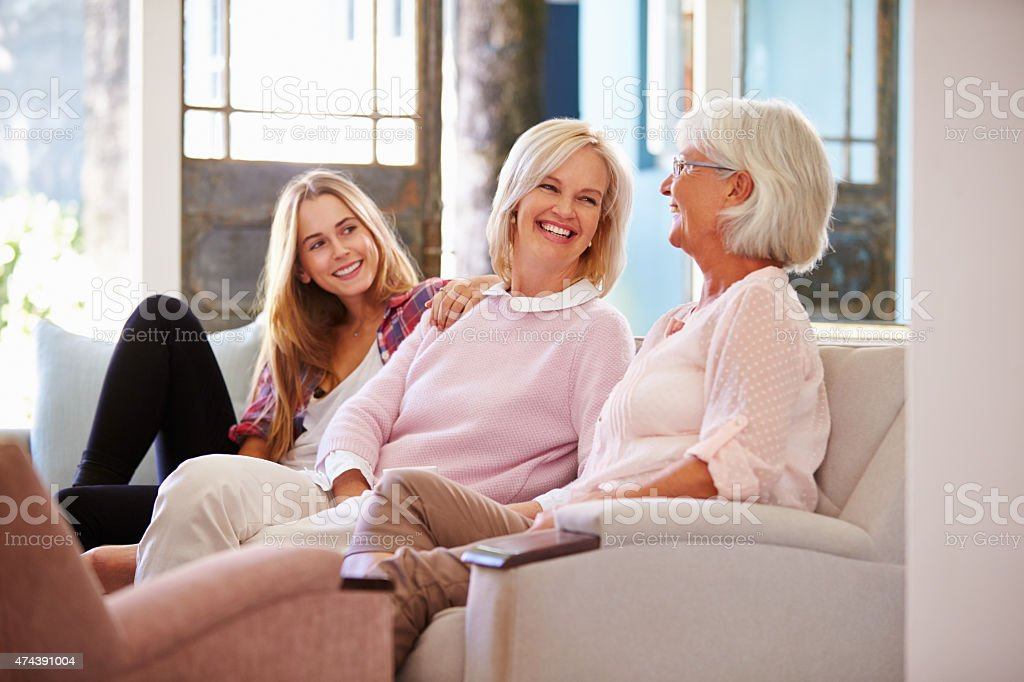 Grandmother With Mother And Adult Daughter Relaxing On Sofa stock photo