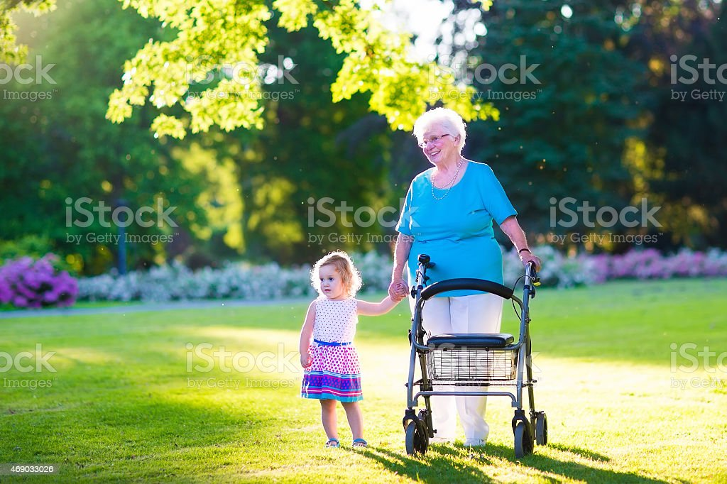 Grandmother with walker and little girl in a park stock photo