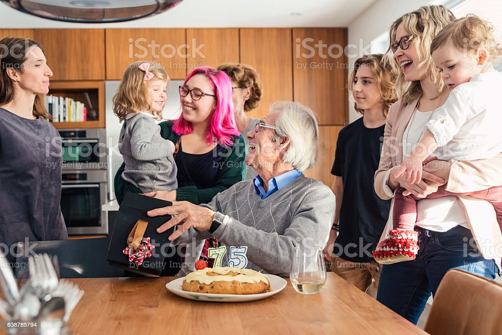 Grandpa 75th birthday celebration with three generation family at home. stock photo