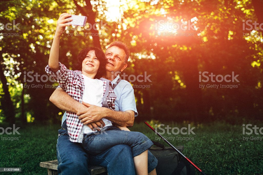 Grandpa and grandson fishing together and making selfie. stock photo