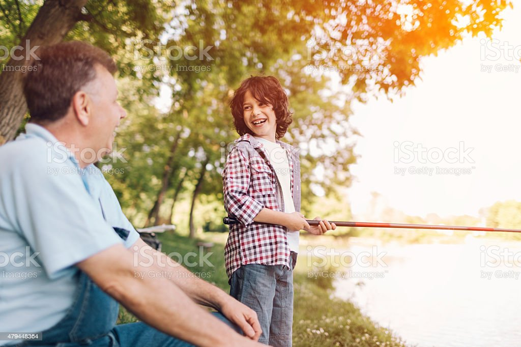 Grandpa and grandson fishing together. stock photo